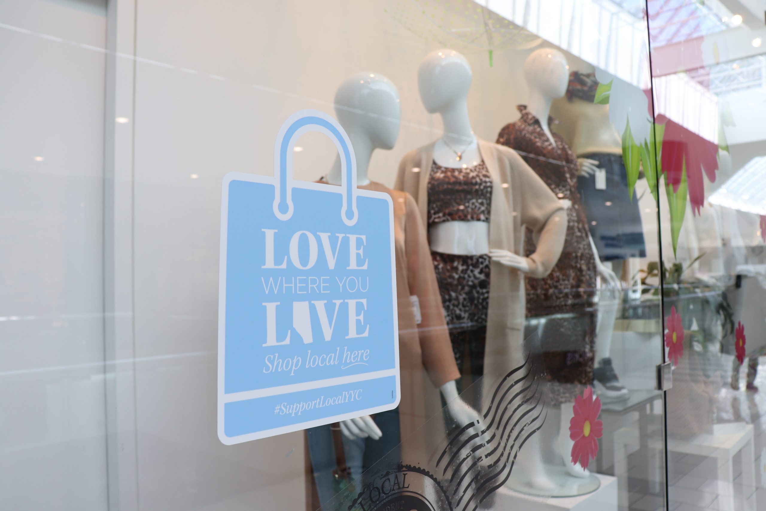 Love Local sticker on storefront with mannequins in the background