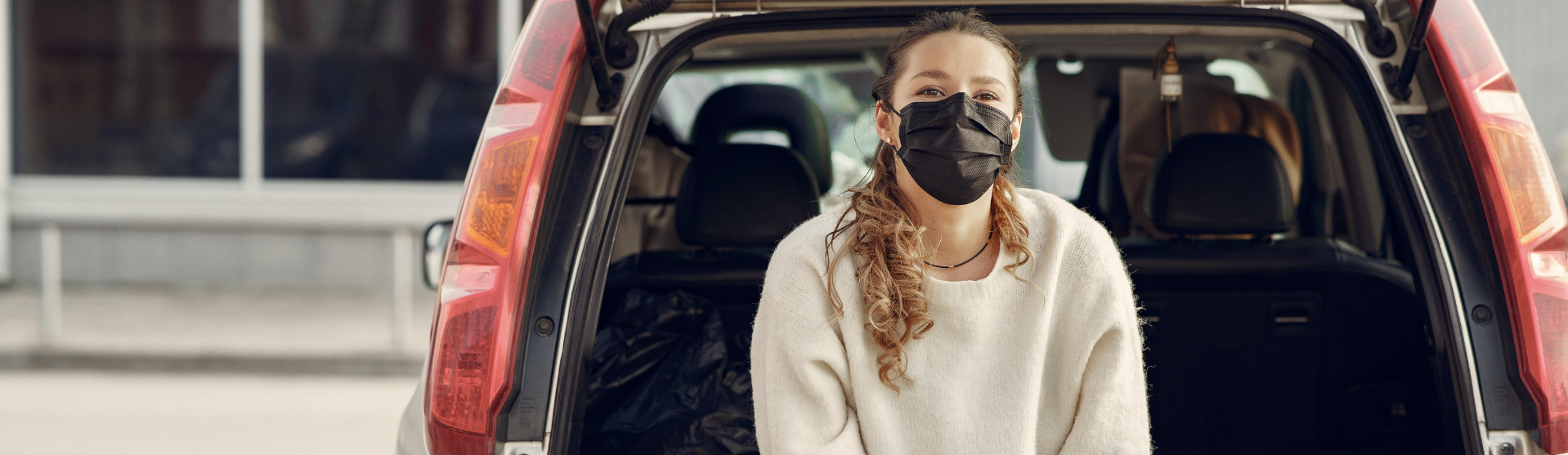 Girl with a face mask behind a car