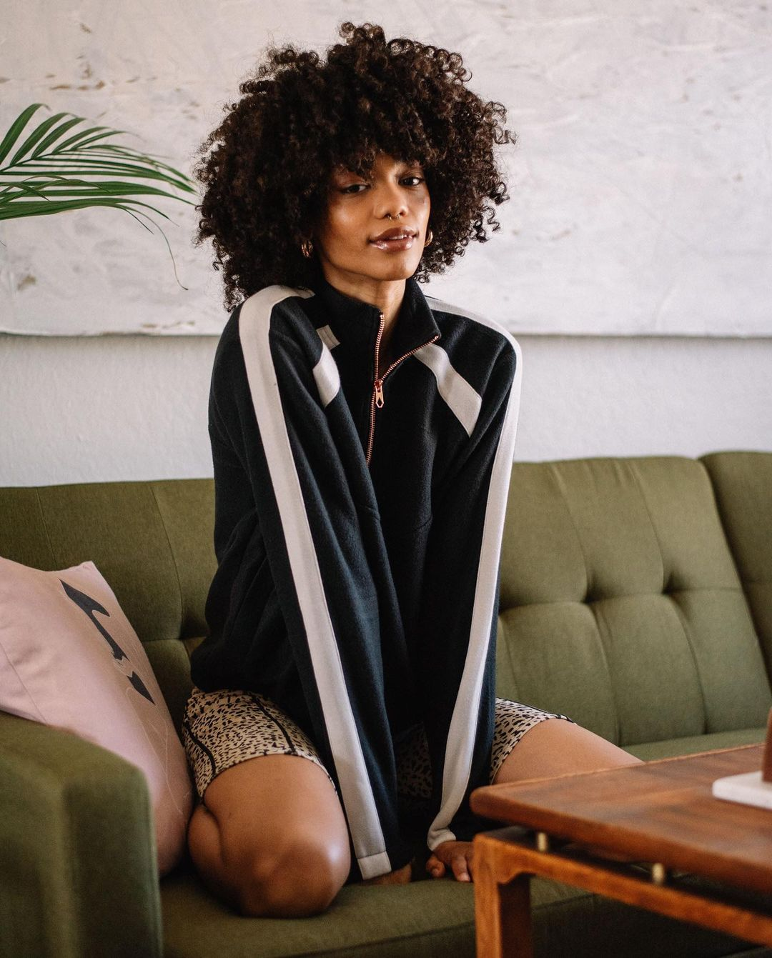 Woman posing on couch in oversized jacket