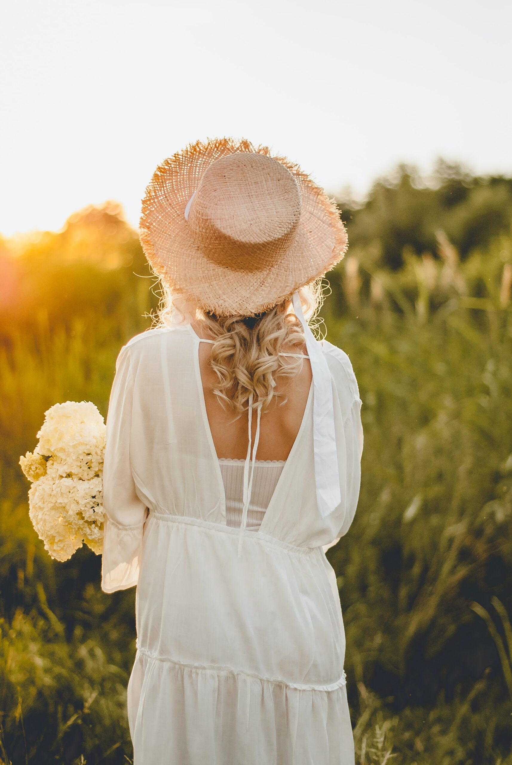 Girl in a white dress and straw hat