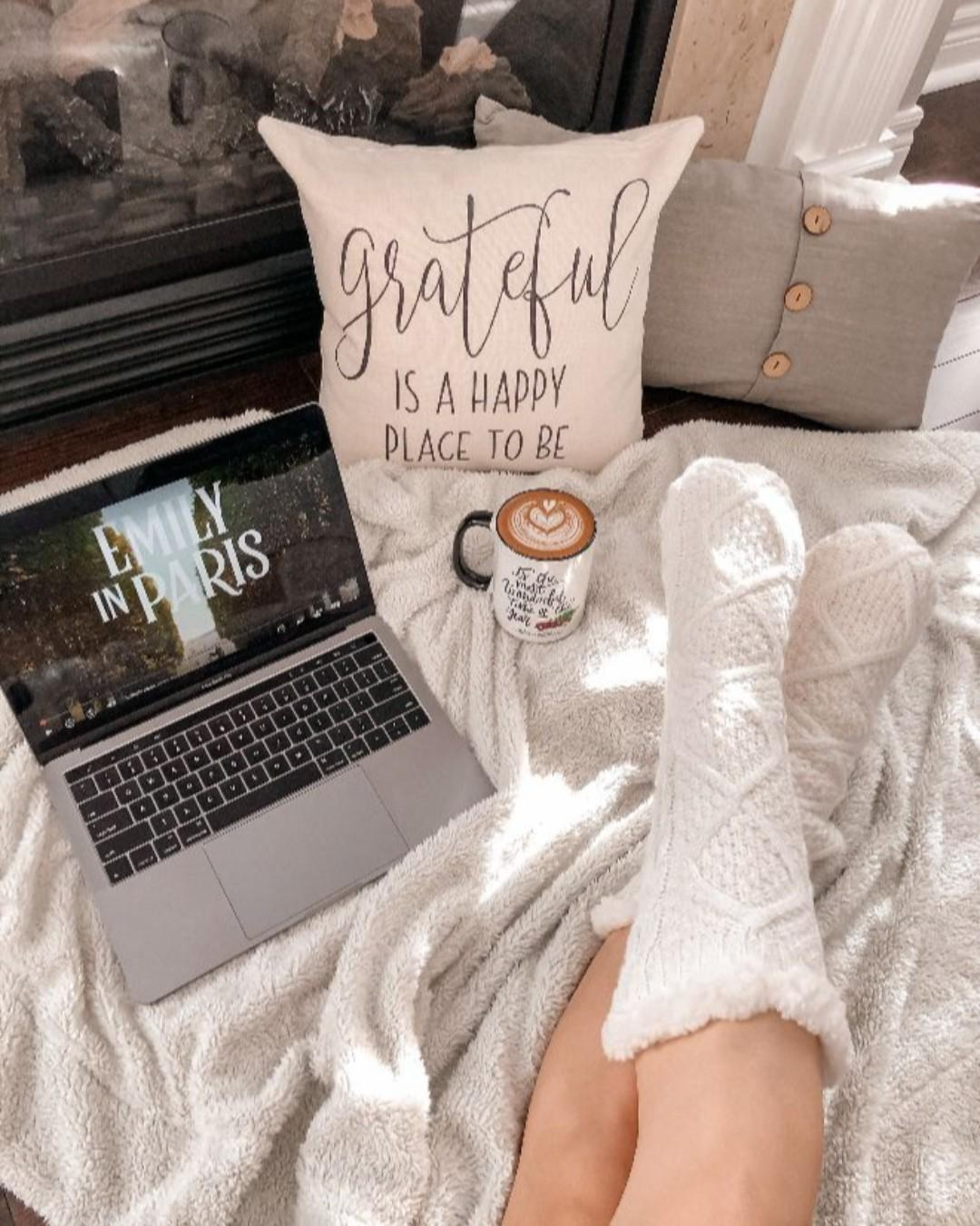 White knit socks in front of a latte and a laptop