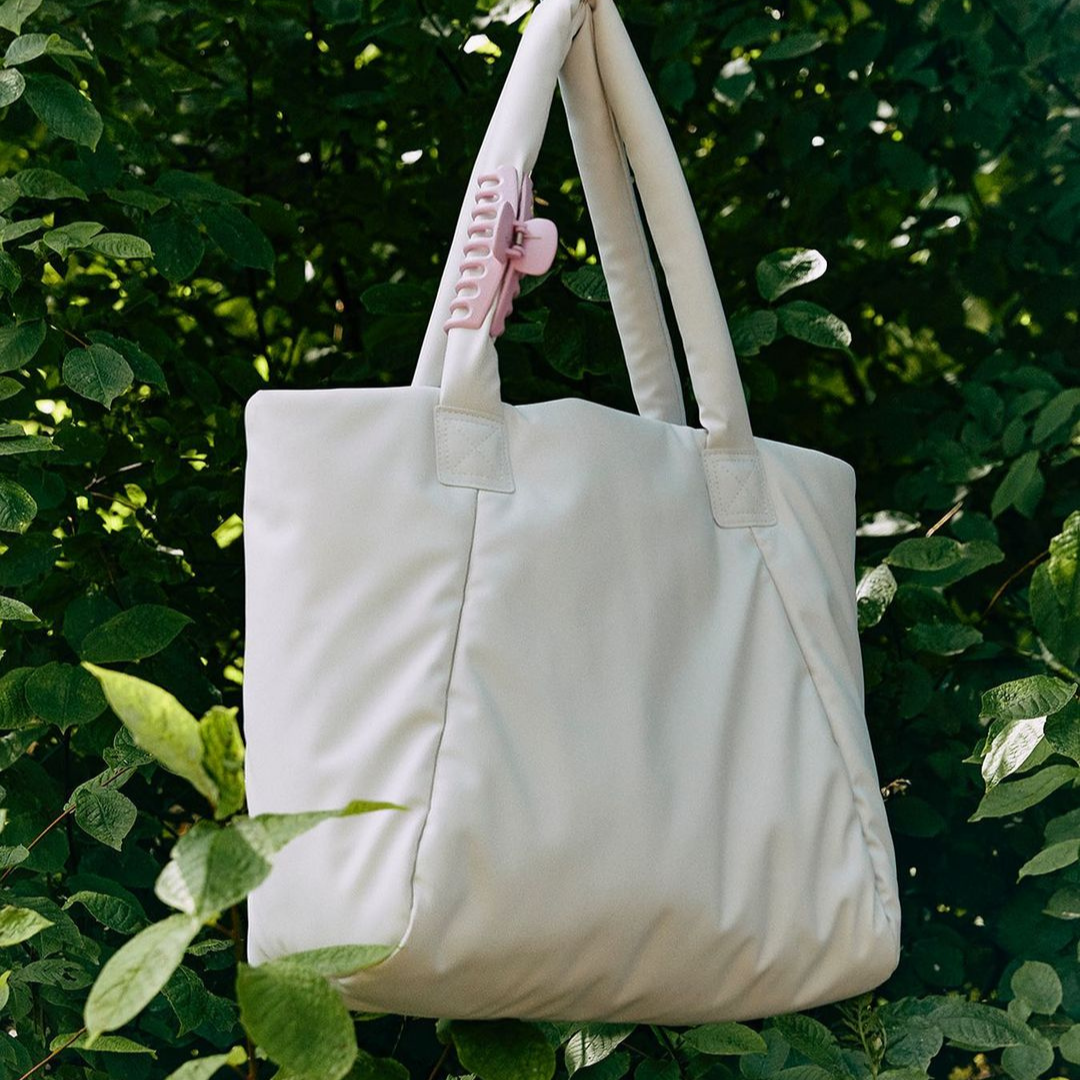 Cream coloured duffel bag with greenery in background