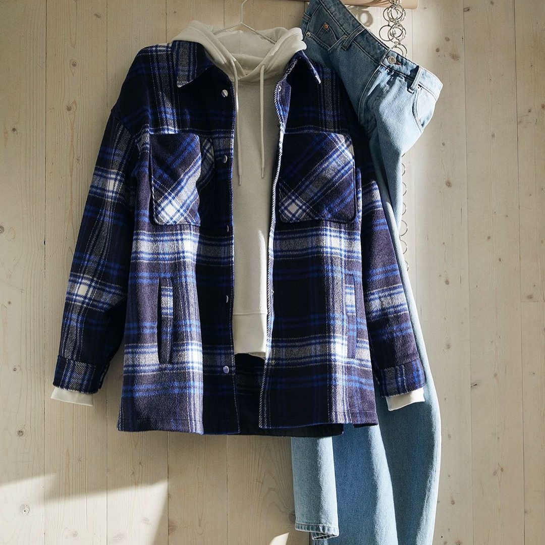 Flannel top layered with a white hoodie underneath and light coloured jeans