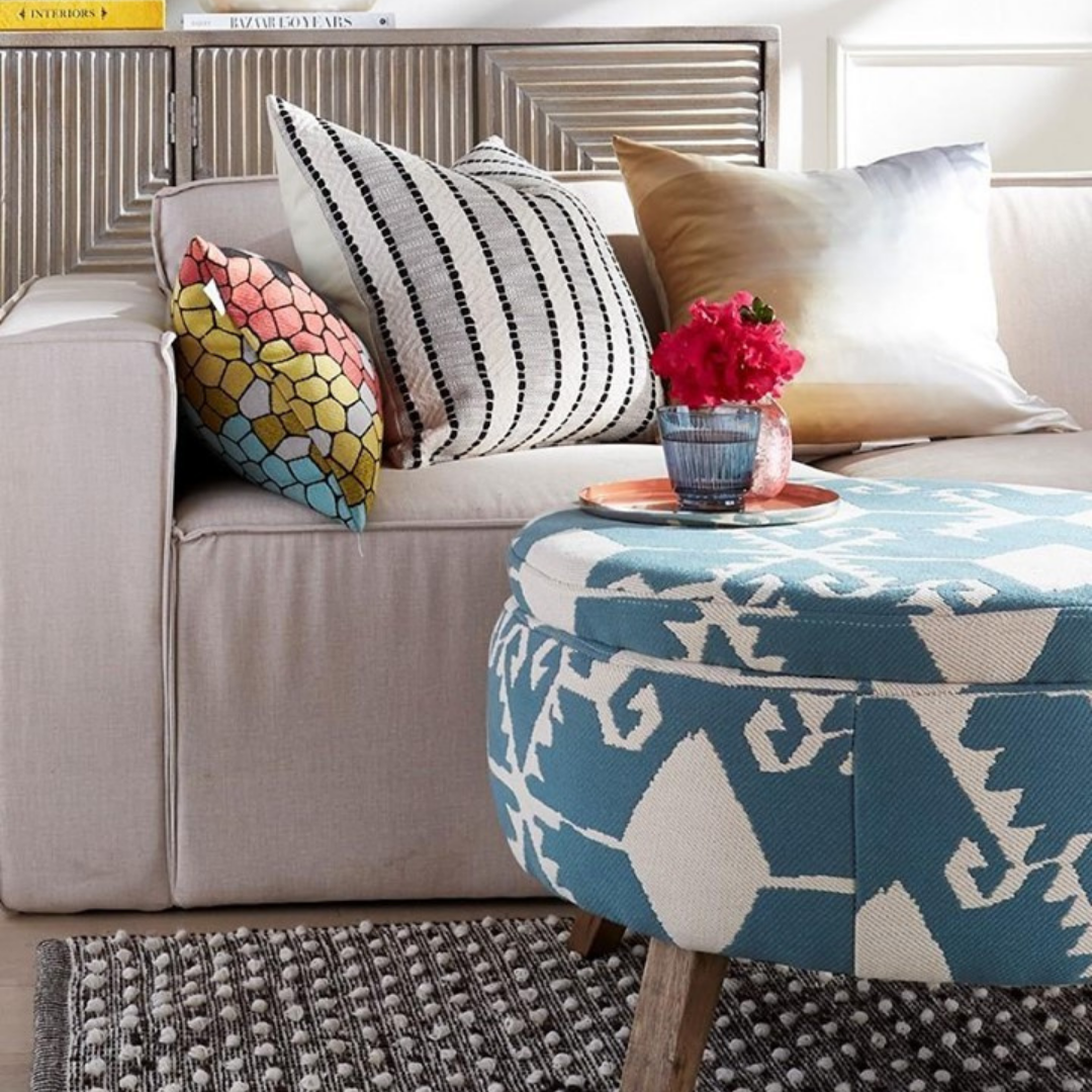 Small round patterned ottoman with vibrant flowers and various patterned pillow accents