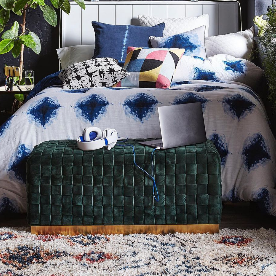 Green velvet ottoman sitting at the end of a blue patterned bed with electronics sitting on the bed